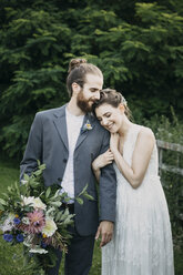 Happy affectionate bride and groom standing on a meadow - ALBF00676