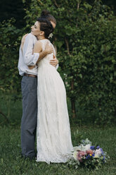 Bride and groom standing on meadow embracing - ALBF00691