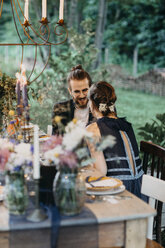 Happy bride and groom sitting at festive laid table outdoors - ALBF00694