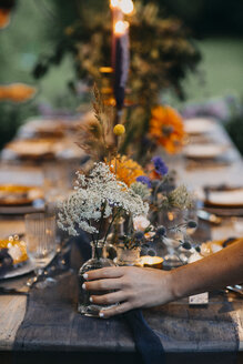 Hand placing flower vase on festive laid table with candles outdoors - ALBF00703