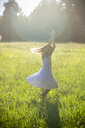 Happy girl dancing on summer meadow at backlight - SARF03953