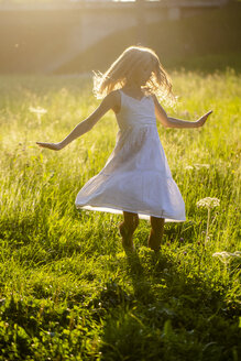 Happy girl dancing on summer meadow at backlight - SARF03959