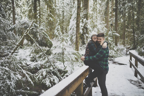 Laughing woman embracing man while sitting on fence in forest at Lynn Canyon Park during winter - CAVF49685