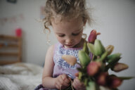 Close-up of girl holding tulips while sitting on bed at home - CAVF49715