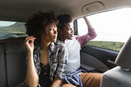Couple looking through window while traveling in car - CAVF49727