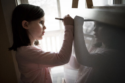 Side view of cute girl drawing on artist's canvas at home - CAVF49790