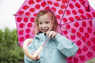 Happy cute girl carrying pink umbrella while standing outdoors during rainy season - CAVF49814