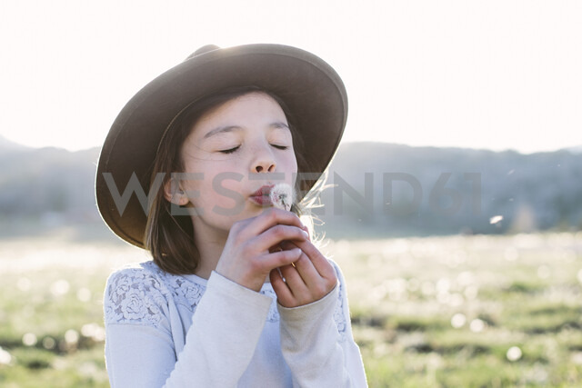 Close-up of girl with eyes closed blowing dandelion seed while standing against sky during sunny day - CAVF49826