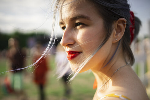 Close-up of smiling thoughtful woman looking away while standing at park - CAVF49862