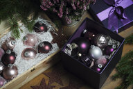 High angle view of colorful baubles with Christmas decorations on table at home - CAVF49871