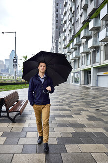 Full length of young businessman with umbrella walking on footpath in city during rainfall - CAVF49895