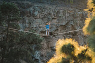 Rear view of man slacklining against mountain during sunset - CAVF49901