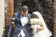 Confetti throwing on happy newlywed couple leaving from church - CAVF49913