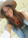 Close-up portrait of happy woman wearing hat while standing on grassy field during sunny day - CAVF49916