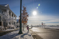Side view of playful girl kicking snow on road against blue sky during sunny day - CAVF49928