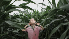 Cute boy looking up while standing amidst crops at farm - CAVF49943