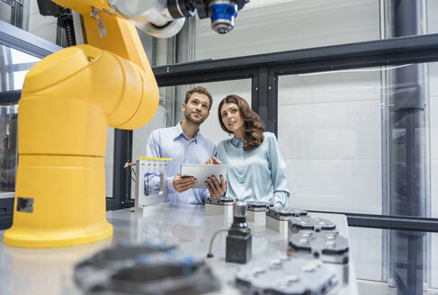 Colleagues in high tech company controlling industrial robots, using digital tablet - DIGF05156