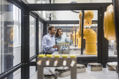 Colleagues in high tech company controlling industrial robots, using digital tablet - DIGF05159