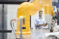 Businessman checking industrial robot in high tech company - DIGF05174