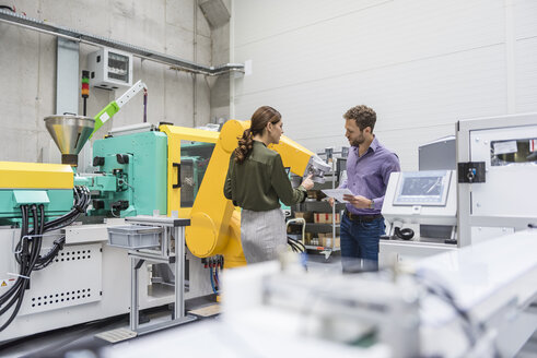 Businessman and woman having a meeting in front of industrial robots in a high tech company - DIGF05228