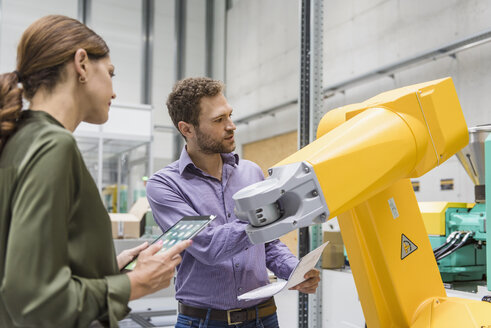 Businessman and woman having a meeting in front of industrial robots in a high tech company - DIGF05231