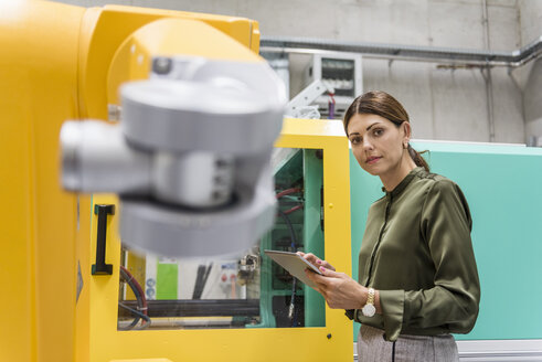 Businesswoman checking industrial robot in high tech company - DIGF05234