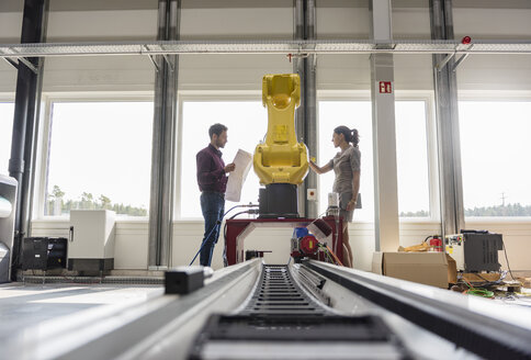 Businessman and woman having a meeting in front of industrial robots in a high tech company - DIGF05255
