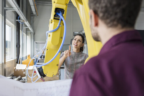 Businessman and woman having a meeting in front of industrial robots in a high tech company - DIGF05258
