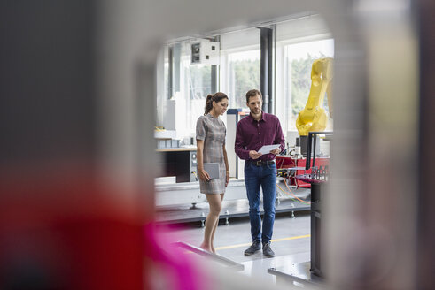 Businessman and woman having a meeting in front of industrial robots in a high tech company - DIGF05261