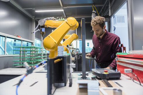 Businessman checking industrial robot in high tech company - DIGF05264