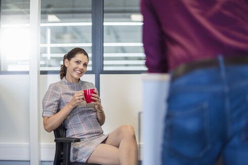 Female employee sitting at desk, talking to colleague - DIGF05270