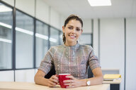 Pretty office worker sitting at desk with red coffee cup - DIGF05273