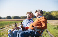 Two old friends sitting in the fields, drinking beer, talking about old times - UUF15479
