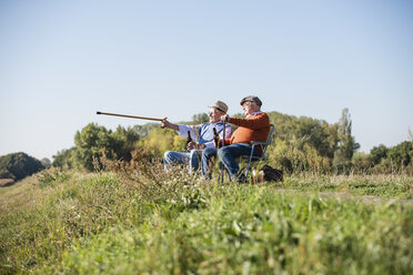 Two old friends sitting in the fields, drinking beer, pointing with walking stick - UUF15482