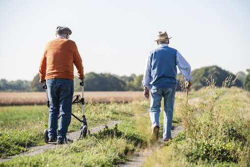 Old friends taking a stroll in the fields with walking stick and wheeled walker, talking about old times - UUF15488