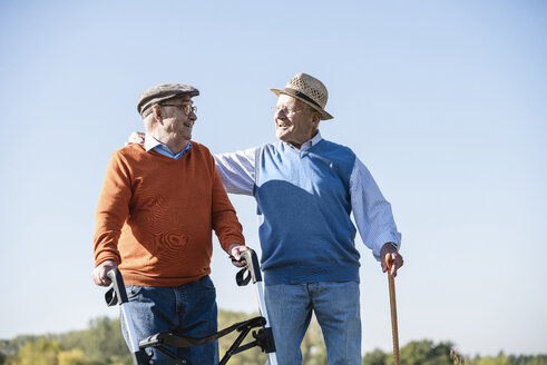 Old friends taking a stroll in the fields with walking stick and wheeled walker, talking about old times - UUF15491