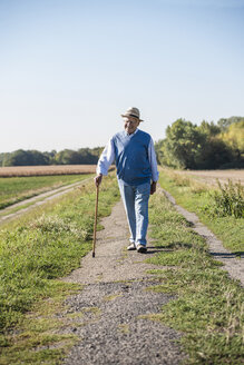 Senior man with a walking stick, walking in the fields - UUF15494