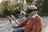 Two old friends sitting by the riverside, using VR glasses - UUF15521
