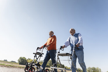 Two old friends walking on a country road, using wheeled walkers - UUF15527