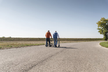 Two old friends walking on a country road, using wheeled walkers - UUF15530