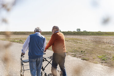 Two old friends walking on a country road, using wheeled walkers - UUF15533