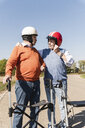 Two old friends wearing safety helmets, preparing for a wheeled walker race - UUF15536