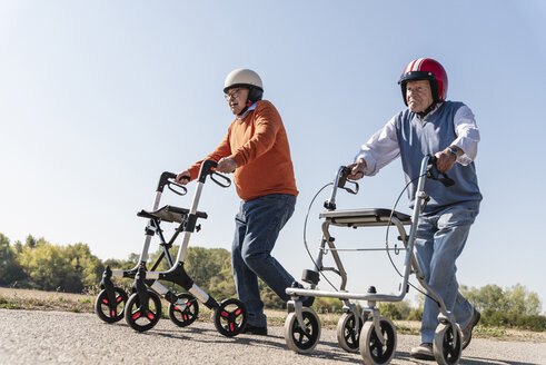 Two old friends wearing safety helmets, competing in a wheeled walker race - UUF15539