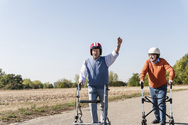 Two old friends wearing safety helmets, competing in a wheeled walker race - UUF15542