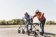 Two old friends wearing safety helmets, competing in a wheeled walker race - UUF15545