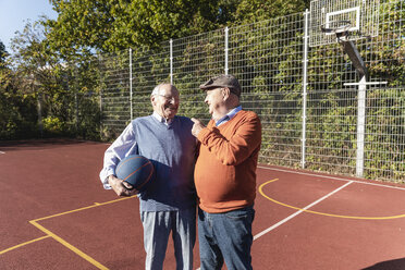 Two fit seniors having fun on a basketball field - UUF15548