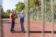 Two fit seniors high fiving on a basketball field - UUF15551
