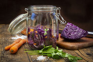 Homemade red cabbage, fermented, with chili, carrot and coriander, preserving jar on wood - LVF07487