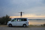 Woman standing on top of the van resting at sunset on the lake - SKCF00539