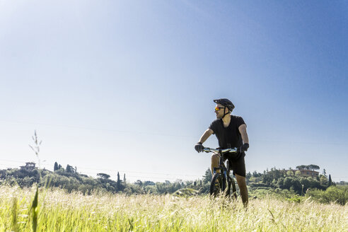 Young man with mountain bike on grassy field against clear sky during sunny day - CAVF49986